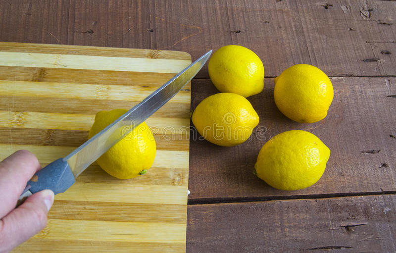 When the lemon is cut,Fresh juicy lemon on top of the salad and fresh for the fish,. Knife and lemon pictures ready to cut on the table,Fresh juicy lemon on top stock photography