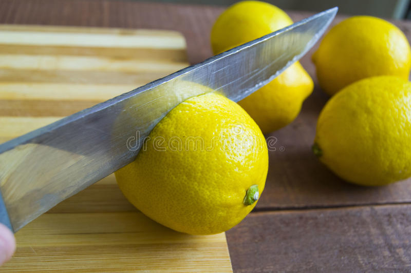 When the lemon is cut,Fresh juicy lemon on top of the salad and fresh for the fish,. Knife and lemon pictures ready to cut on the table,Fresh juicy lemon on top royalty free stock photos