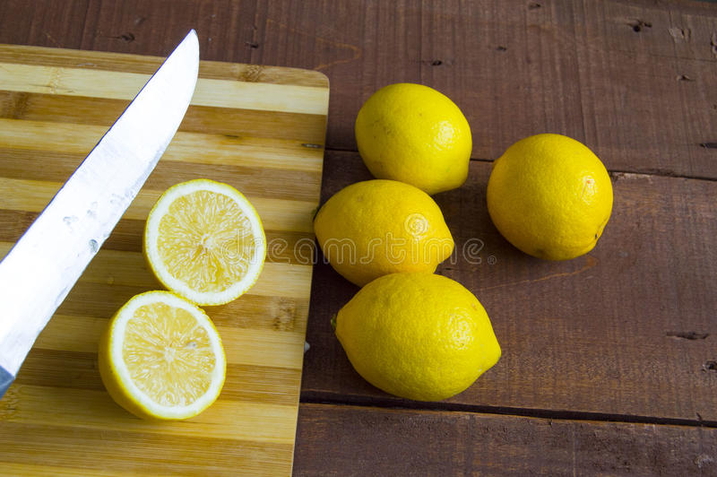 When the lemon is cut,Fresh juicy lemon on top of the salad and fresh for the fish,. Knife and lemon pictures ready to cut on the table,Fresh juicy lemon on top stock photos