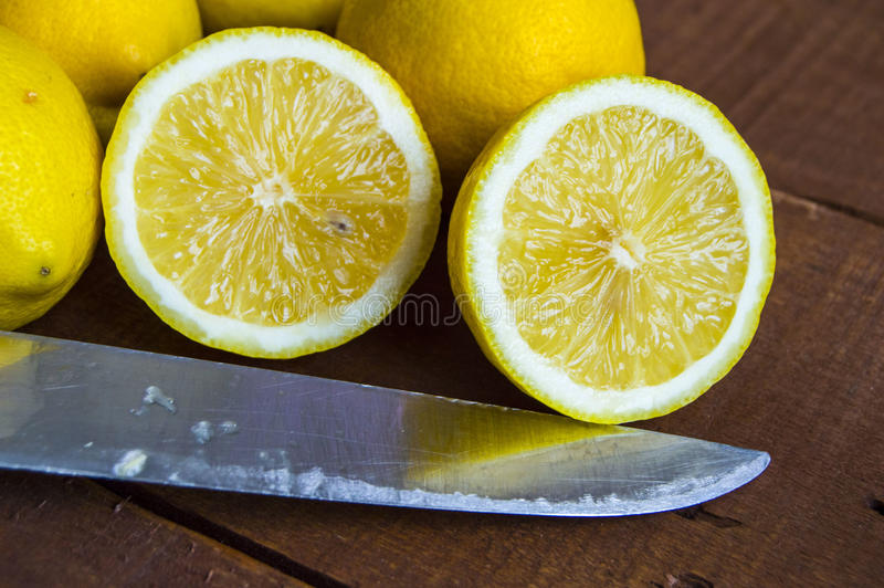 When the lemon is cut,Fresh juicy lemon on top of the salad and fresh for the fish,. Knife and lemon pictures ready to cut on the table,Fresh juicy lemon on top stock image