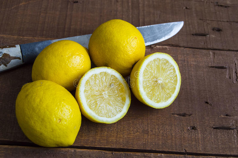 When the lemon is cut,Fresh juicy lemon on top of the salad and fresh for the fish,. Knife and lemon pictures ready to cut on the table,Fresh juicy lemon on top royalty free stock image