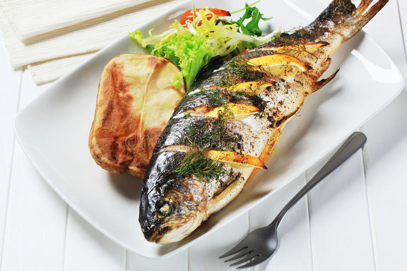 Lemon dill trout with baked potato stock images