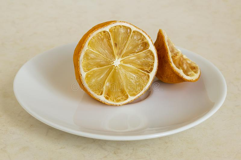 Lemon dried in the fridge. Stale citrus on a white saucer. Foods forgotten in the home refrigerator royalty free stock photo