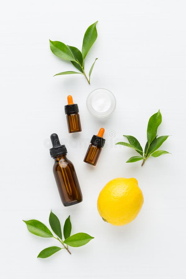 Lemon essential oil, cream on white background from top view. stock image