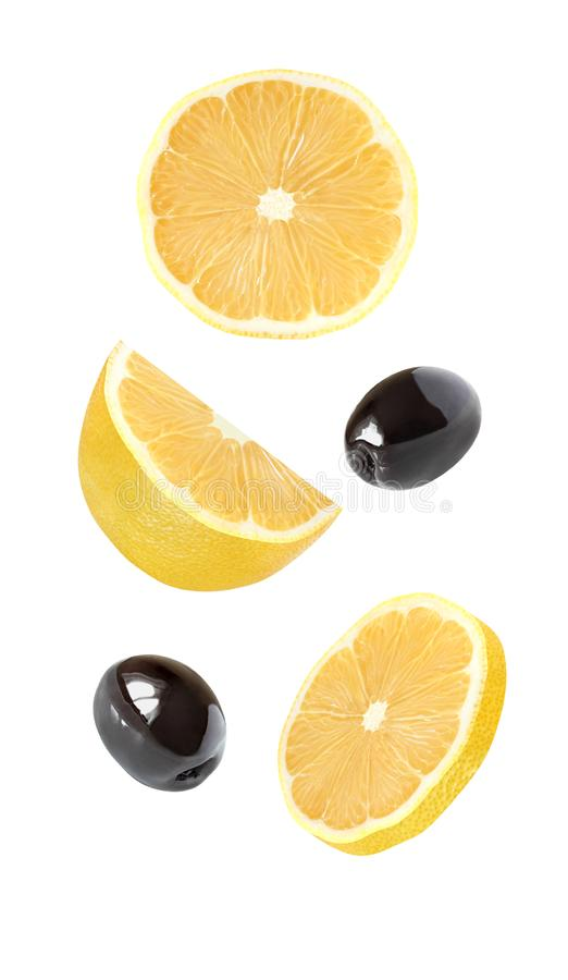 Lemon falling, hanging, flying whole and half piece of fruits and black olives isolated on white background with clipping path stock photos
