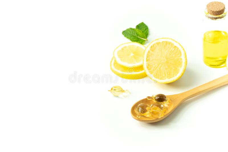 Lemon fruit juice with bottle and peppermint leaf with wood spoon and vitamin on white background in beauty spa skin treatment hea royalty free stock image