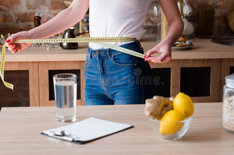 Lemon ginger detox diet weight loss slim waist. Lemon and ginger detox diet for weight loss. slim and fit body. woman measuring her waist with a tape royalty free stock photos