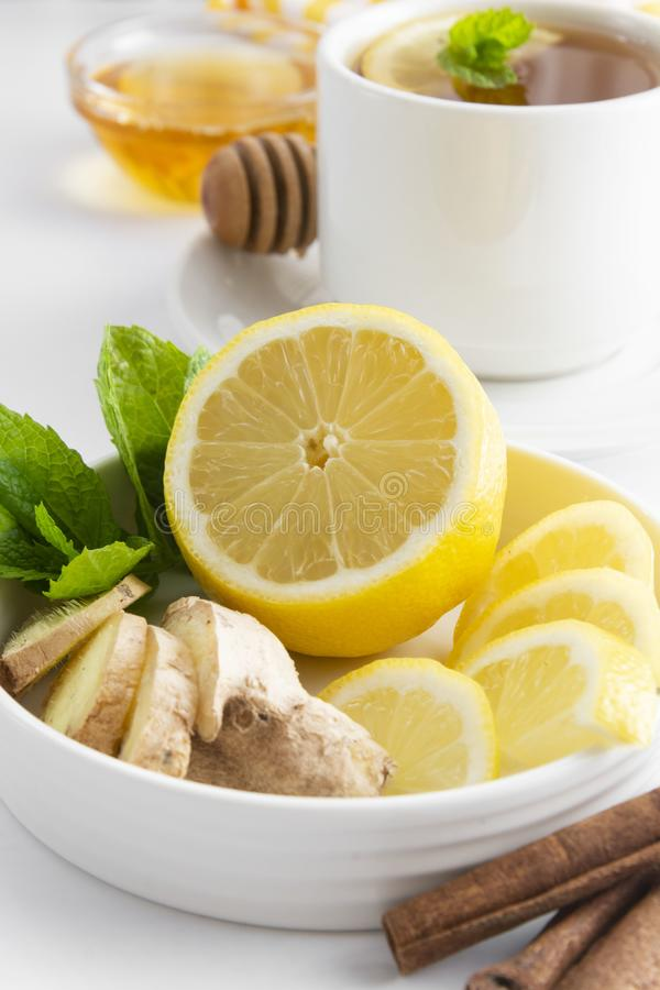 Lemon and ginger slices with mint white background copy space. Autumn, winter tea ingredient stock photography