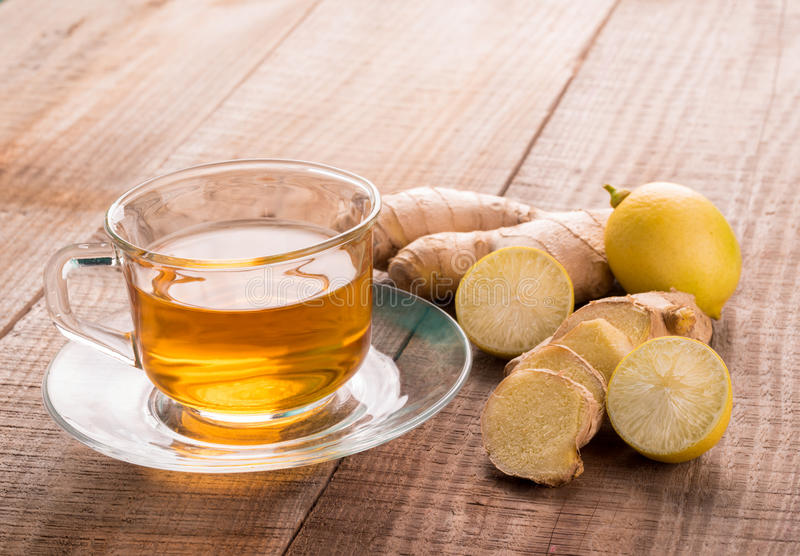 Lemon and ginger tea. A glass cup of lemon and ginger tea with ingredients alongside the saucer, all placed upon a grainy wooden table stock images