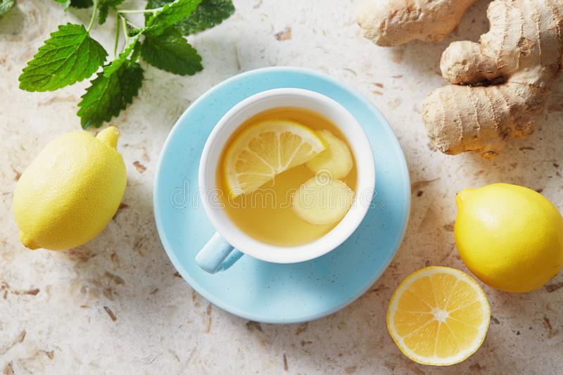 Lemon and ginger tea with honey. Cup of hot honey lemon tea with fresh ginger root stock photos