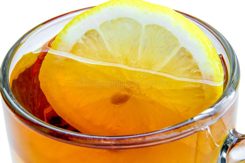 Lemon in a glass cup of tea on a white background royalty free stock photos