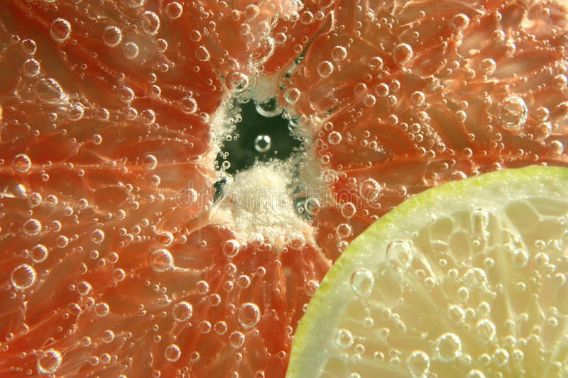 Lemon and grapefruit submerged. In sparkling water stock photo
