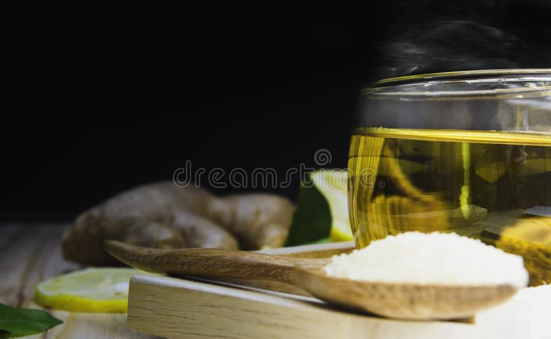 Lemon honey tea mixed with ginger in a clear glass with smoke, with a spoon and  brown sugar and hemp bag placed in a wooden tray. On a brown wood background royalty free stock photography