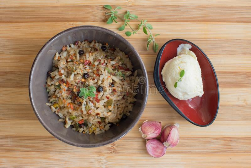 Brown rice risotto with oregano leaves on ceramic plate and lemon ice cream dessert with basil leaves over wooden countertop royalty free stock photography