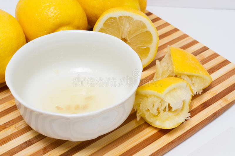 Lemon juice in bowl. Lemon juice squeezed into a white bowl resting on a cutting board stock images