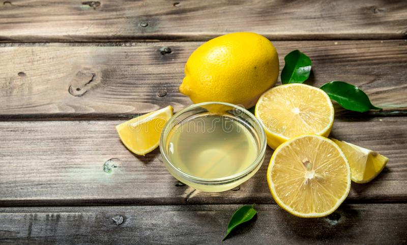 Lemon juice in the bowl. On wooden background stock images