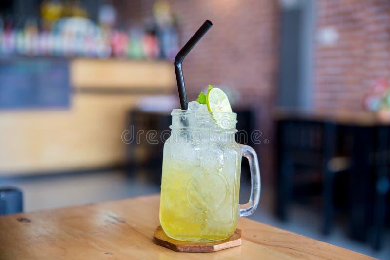 Lemon juice with honey on wooden table. Lemon fizz in a glass. Honey and lemon soda of drink summer. Honey lemon drink on the cafe table stock photo