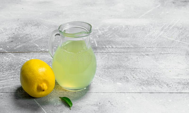 Lemon juice in the pitcher. On rustic background stock photos