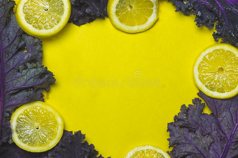 Lemon and Kale Frame on Yellow Background. With Center Copy Space royalty free stock photography