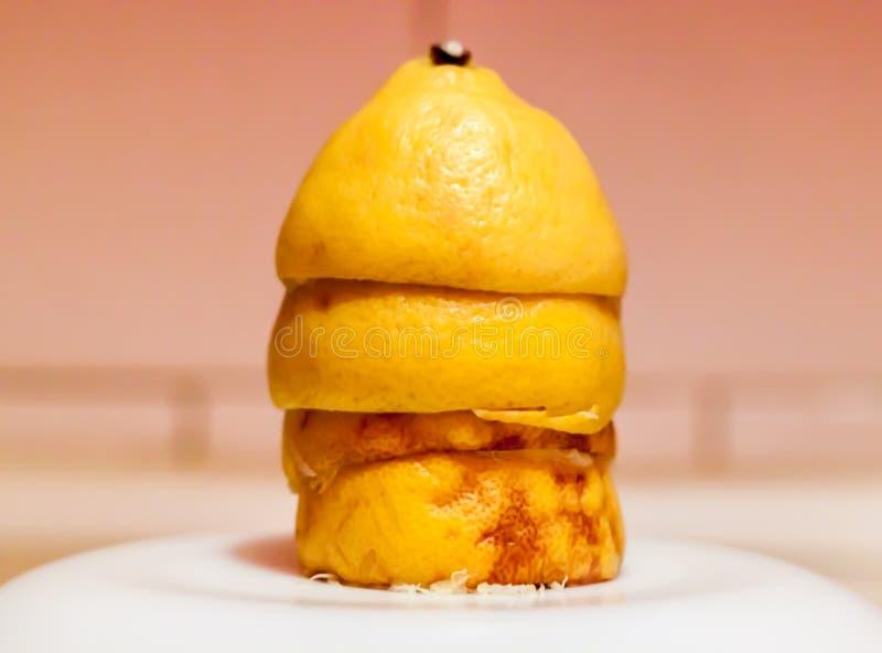 Lemon in kitchen. Lemon`s tower on white plate in kitchen royalty free stock image