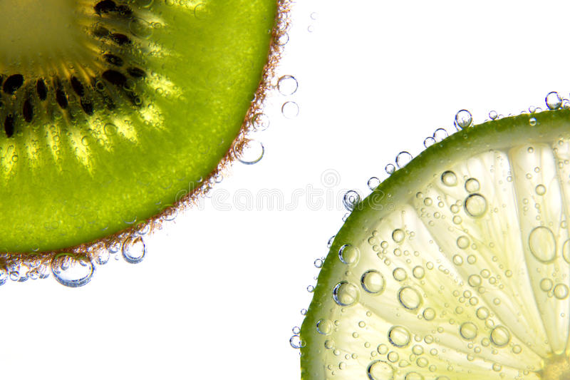 Lemon and kiwi slices with bubbles stock image