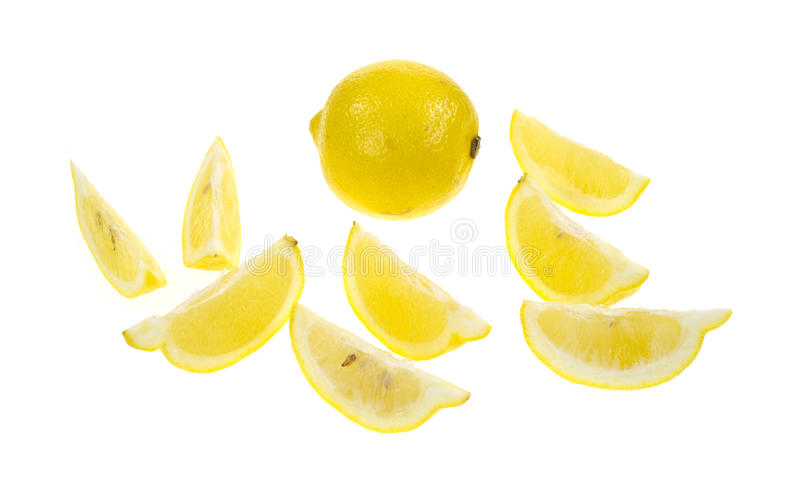 Lemon with lemon wedges. A whole lemon in the background with several wedges in the foreground on a white background stock photo