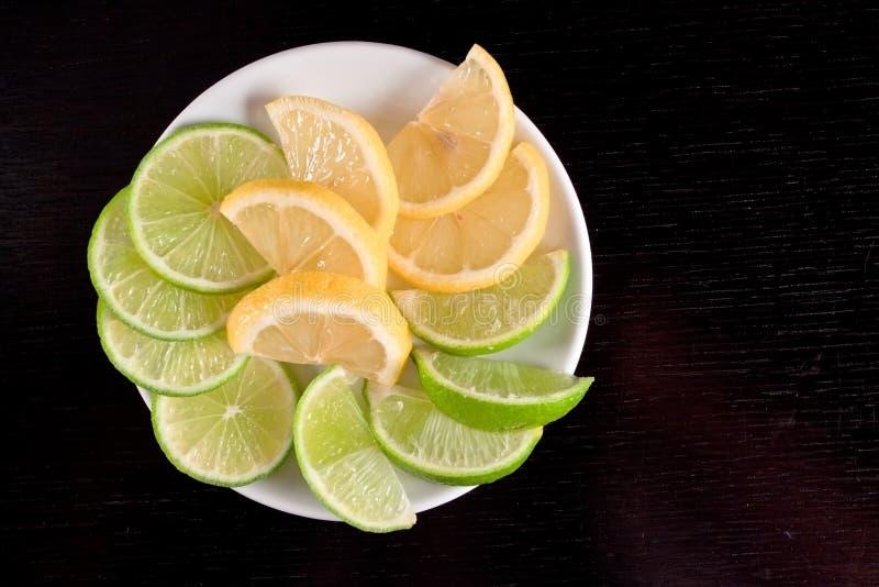 Lemon and lime slices on black wood table.