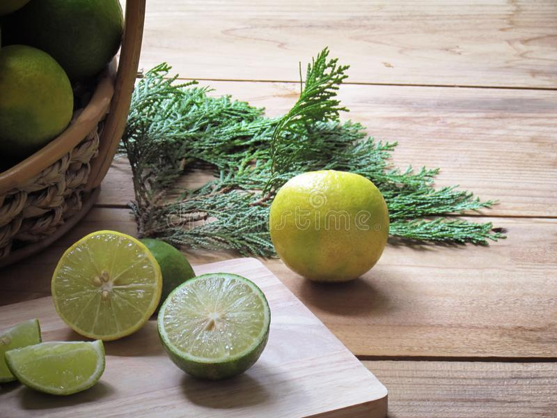 Lemon, lime slices are placed on a cutting board and fresh lemon are in a basket stock photos