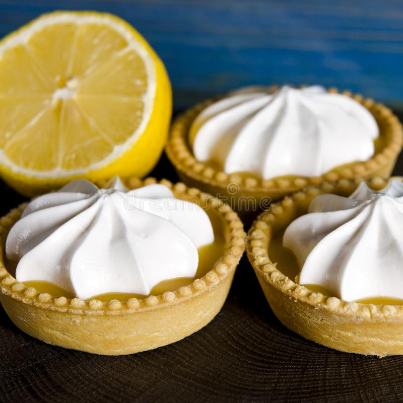 White aircake with lemon filling and lemon on a wooden table. Lemon meringue pie. small lemon meringue pie dessert shortcrust pastry with lemon custard filling stock image