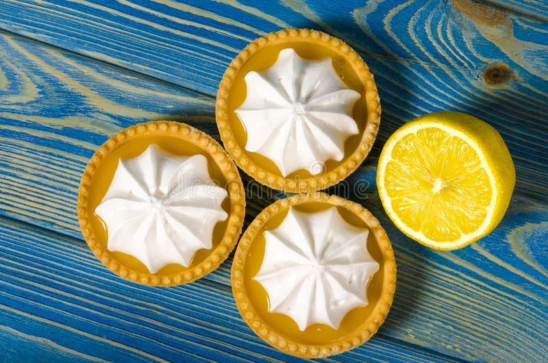 White aircake with lemon filling and lemon on a wooden table. Lemon meringue pie. small lemon meringue pie dessert shortcrust pastry with lemon custard filling royalty free stock image