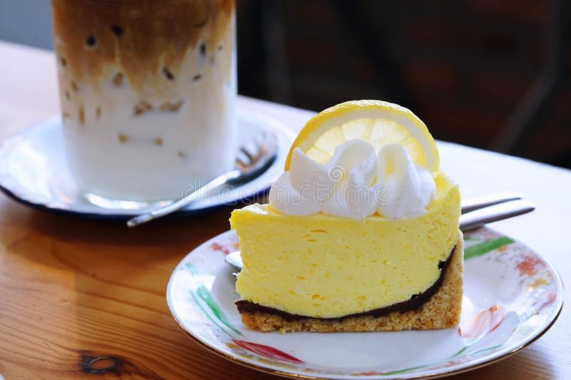 A Lemon meringue pie topped with a large fresh slice lemon placed in white plate and on wooden table with cafe environment. stock images