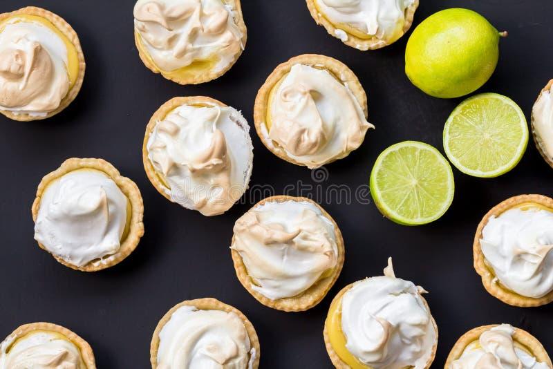 Lemon meringue tartlets made with lime isolated on black surface - overhead image close up. Lemon meringue tartlets made with lime isolated on black surface royalty free stock image