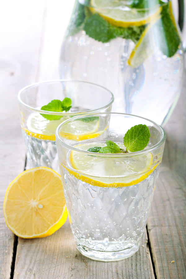 Lemon and mint fizz. In jar and glasses stock images