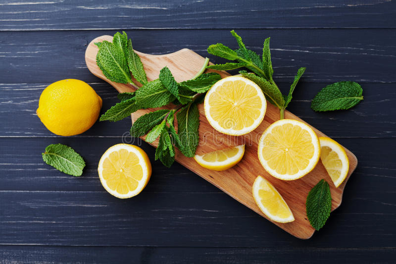 Lemon and mint leaves served on wooden kitchen board on black rustic table, ingredient for summer cocktails and lemonade. Top view stock photos