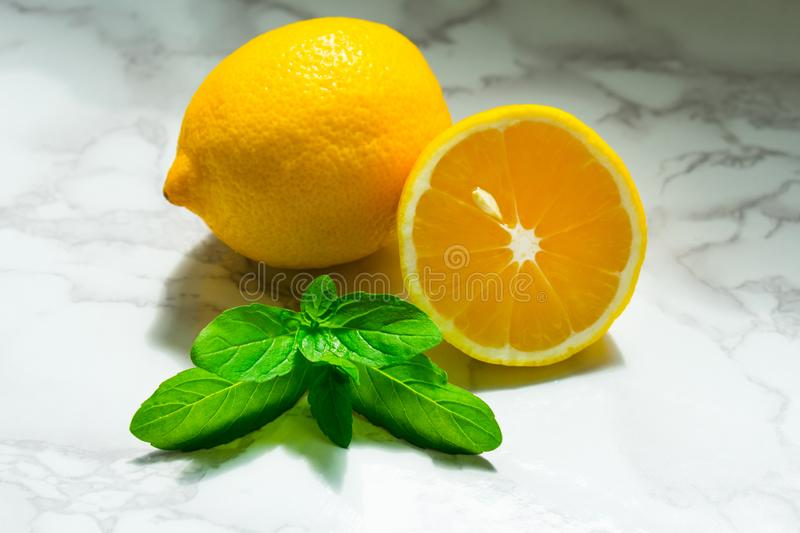 Lemon and mint are on the marble tabletop. Lemon and Mint on marble countertop royalty free stock photos