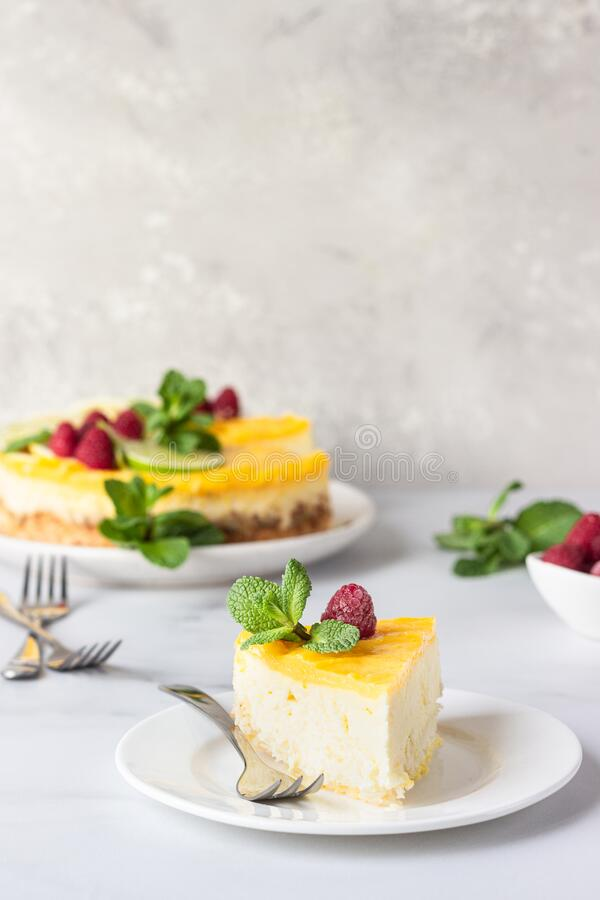 Lemon mousse vanilla cheesecake with lemon curd decorated by lemon and lime slices, frozen raspberry and mint. stock photography