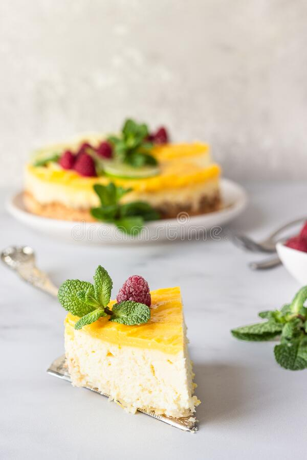 Free Lemon Mousse Vanilla Cheesecake With Lemon Curd Decorated By Lemon And Lime Slices, Frozen Raspberry And Mint. Stock Images - 169285964
