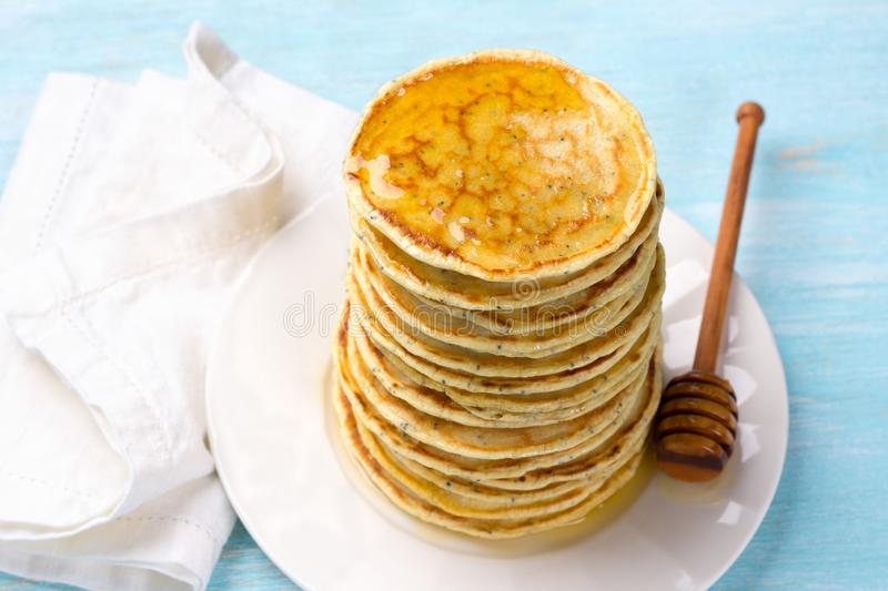 Lemon pancakes with poppy seeds and honey on a blue background stock photo