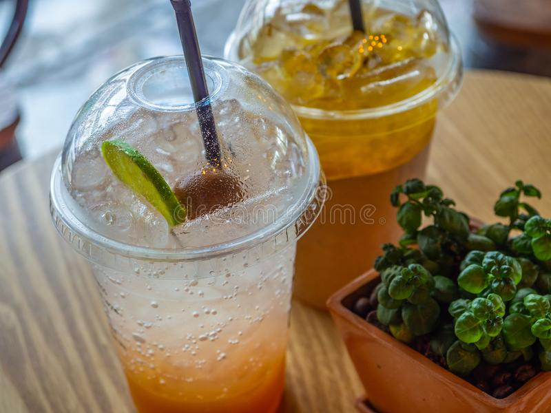 Lemon and Plum soda in transparent plastic cup. On table in resturant royalty free stock photo
