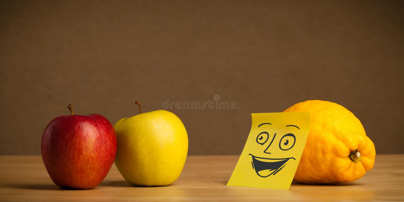 Lemon with post-it note smiling at apple. Lemon with sticky post-it note looking happy at apple royalty free stock image