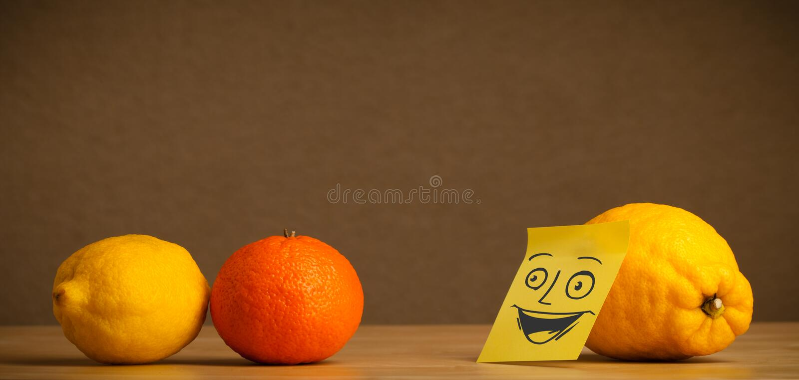 Lemon with post-it note smiling at citrus fruits. Lemon with sticky post-it note looking happy at citrus fruits stock photography