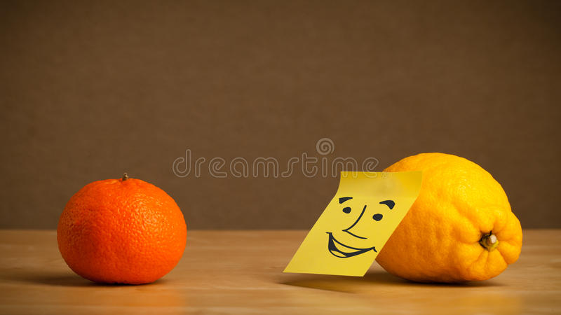Lemon with post-it note smiling at orange. Lemon with sticky post-it note looking at orange stock images