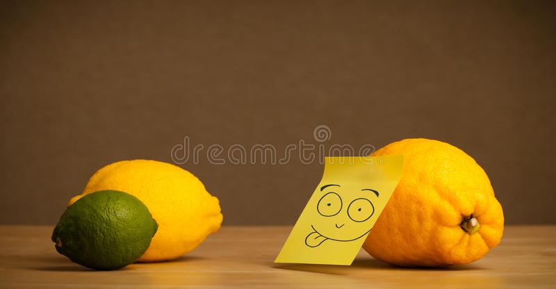 Lemon with post-it note sticking out tongue to citrus fruits. Lemon with sticky post-it note showing tongue to citrus fruits stock photo