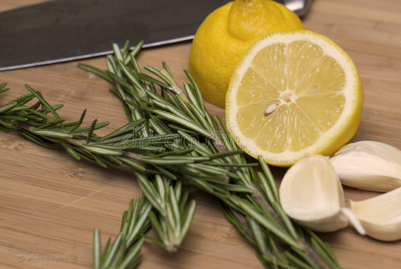 Lemon, Rosemary and Garlic on cutting board stock images