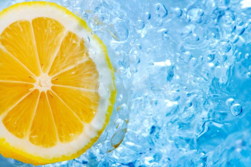 Lemon slice in blue water royalty free stock image