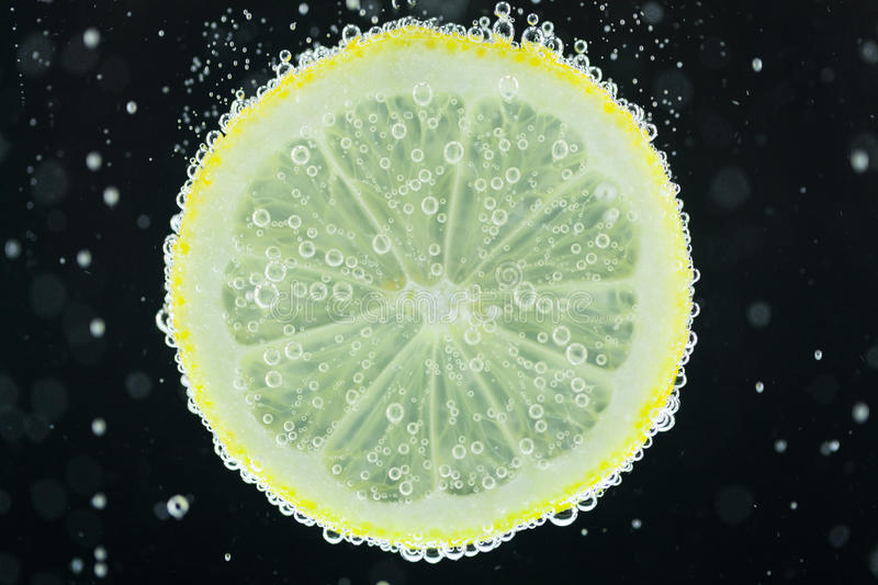 Lemon slice diving into water stock images