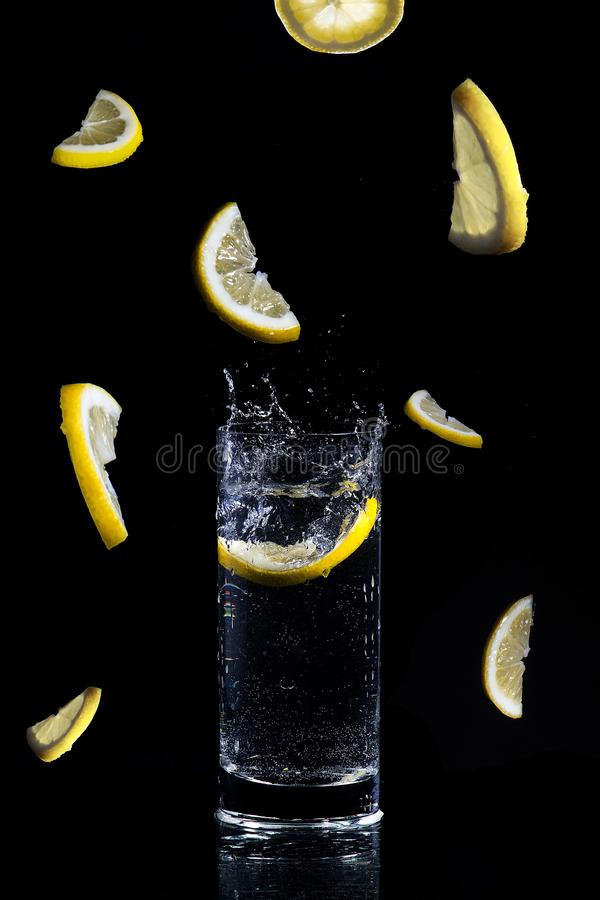 Lemon slice splases in glass o water Freeze time concept, Lemon in a glass, freezing time, falling lemons, low key. royalty free stock photo
