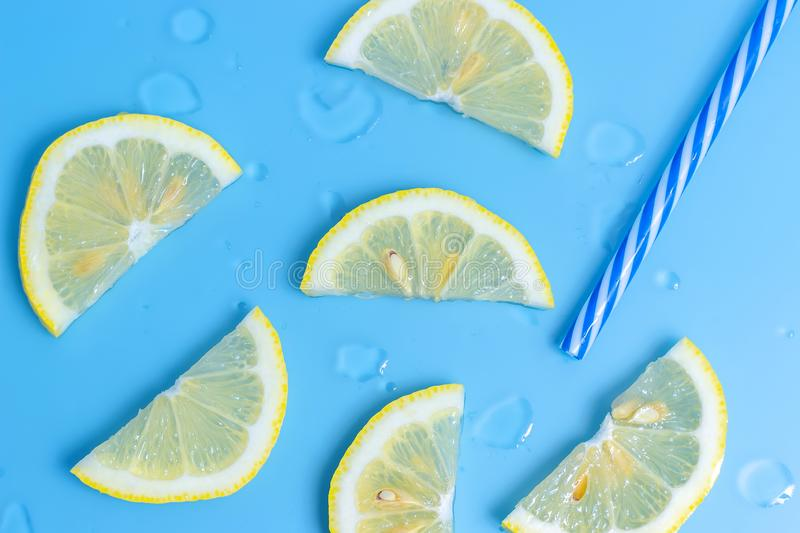 Lemon slices on blue background, top view. Summer concept stock photography