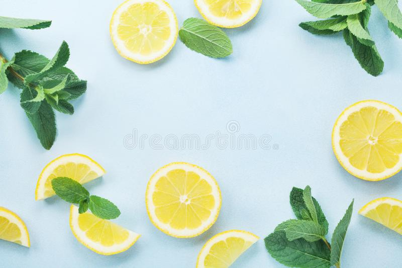 Lemon slices and mint leaves on blue pastel table top view. Ingredients for summer lemonade and cocktail. Flat lay style. royalty free stock photos