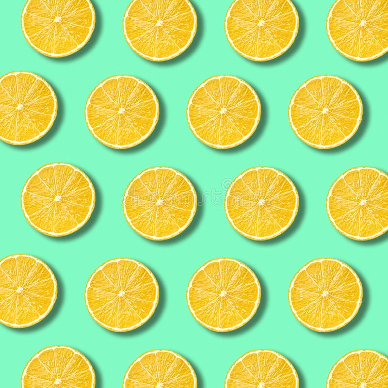 Lemon slices pattern on vibrant green color background royalty free stock photos